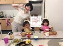 ピースサインの女性とご飯を食べる子どもたち