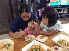 子どもと一緒に野菜料理を食べている様子